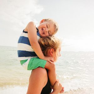 Smiling little boy and his mother enjoy beautiful sunny day on the beach, during their vacation